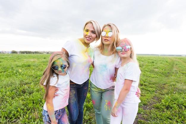 ホーリー祭、休日、幸福の概念-色の若い十代の若者たちと女性は屋外で楽しい