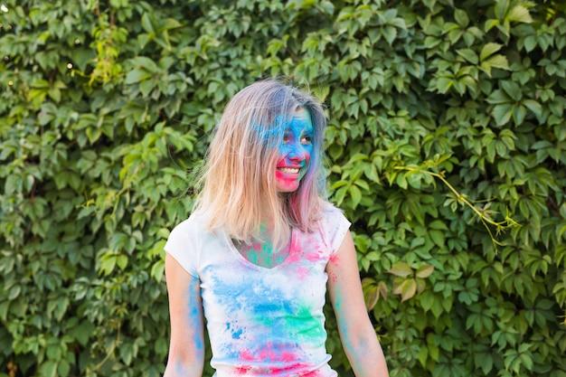 Фестиваль холи, праздники и люди концепции - молодая женщина веселится на фестивале холи.