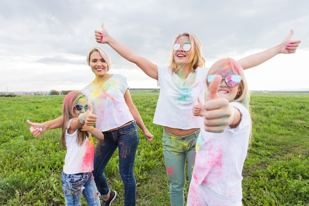 Holi festival, holidays and happiness concept - young teens and women in colors have fun outdoor