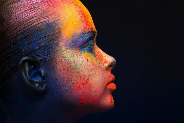 色のホーリー祭。創造的なメイクアップと女性の顔アート。ペイントの明るくカラフルなミックスと若者のファッションモデルの肖像画。