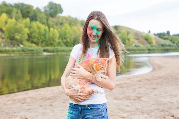 Фестиваль холи, летний туризм и концепция природы - молодая привлекательная девушка с кошкой на естественном фоне