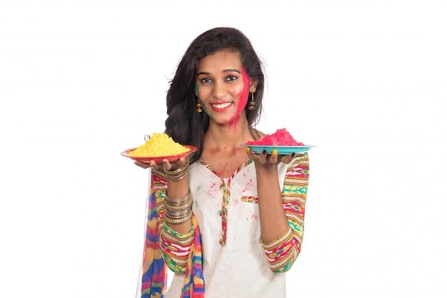 Красивая маленькая девочка держа напудренный цвет в плите по случаю фестиваля holi.