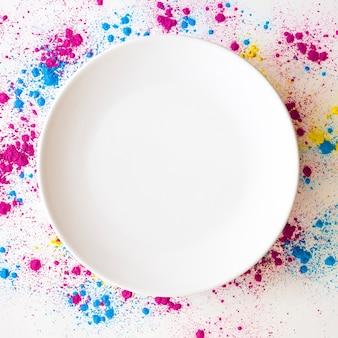 白い空の空のプレートの周りにholi色の粉