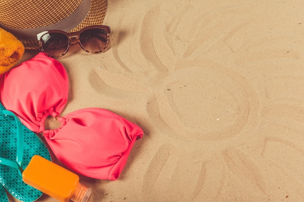 Holiday accessories on sand beach background