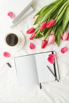 휴일 및 축하. 봄 방학. 흰색 침대에 튤립과 커피 한잔 열린 빈 노트북의 상위 뷰