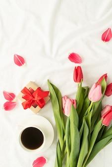 휴일 및 축하. 흰색 침대에 핑크 튤립, 커피 컵 및 선물 상자의 상위 뷰, 평평하다