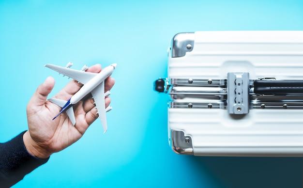 Праздник и путешествие с рукой, держащей макет самолета на сумке чемодана.