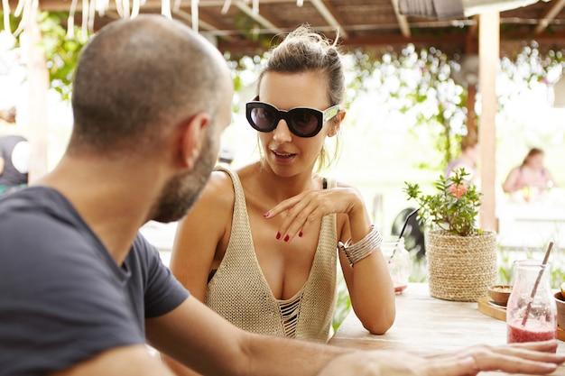 Отпуск и каникулы два человека мило беседуют, сидя за барной стойкой со свежими напитками.