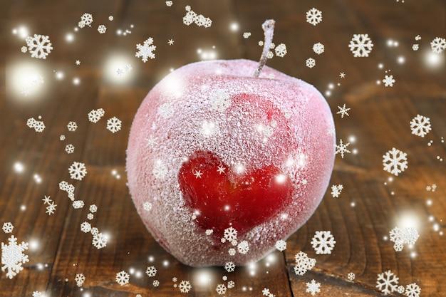木製の背景につや消しの心と休日のリンゴ