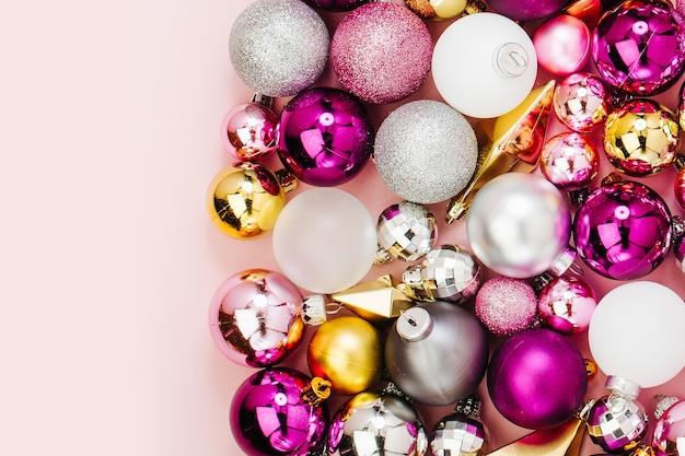 Праздничная композиция со стильными рождественскими блестящими шарами и золотыми кристаллами на пастельно-розовом фоне. плоская планировка, вид сверху