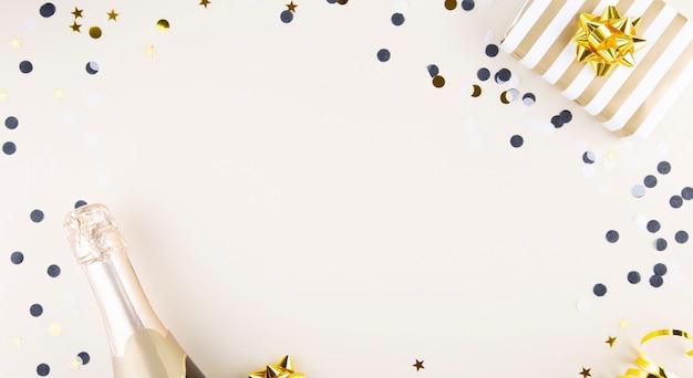 Атрибуты праздника. бутылка шампанского, конфетти и подарок на новый год на бежевом фоне