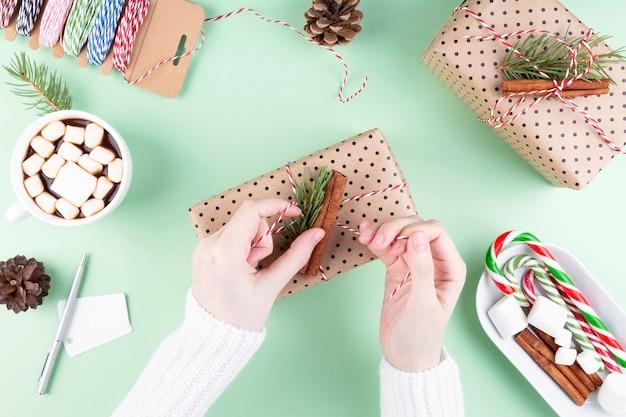 휴일 속성. 소녀는 선물, 녹색을 포장합니다.