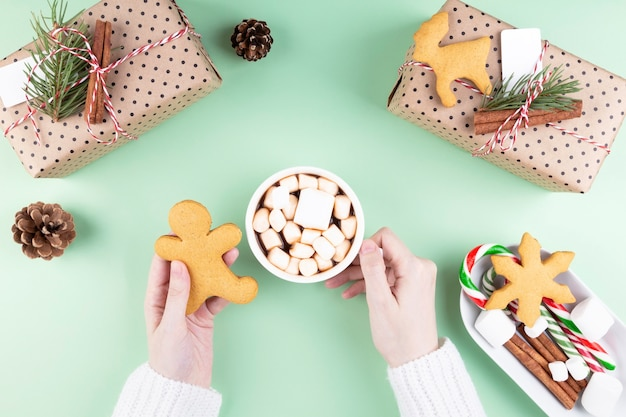 Holiday attributes. woman drinks cocoa with marshmellow and carrot, packing gifts