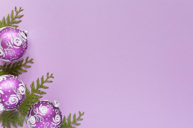 휴일 배경, 크리스마스 공, 라일락 배경에 있는 thuja 잔가지, 평평한 평지, 위쪽 전망