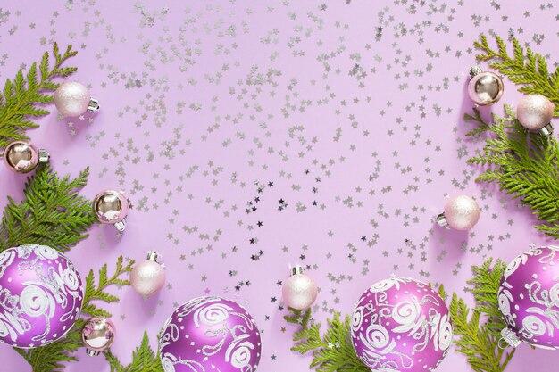 ホリデー背景、クリスマス ボール、thuja の小枝、ライラック色の背景にキラキラ銀の星、フラット レイアウト、トップ ビュー