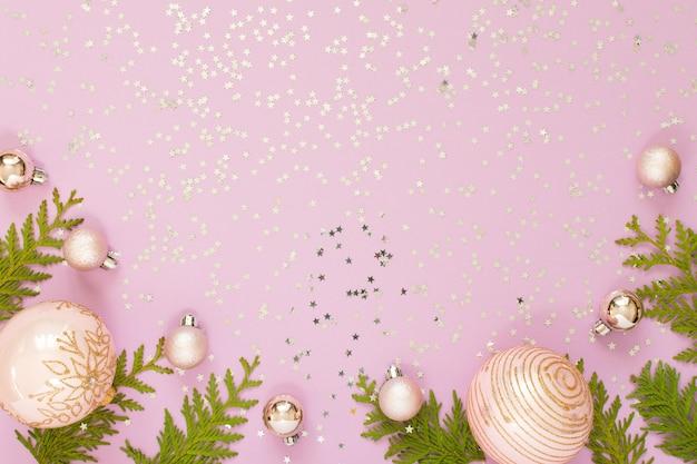 Праздничный фон, новогодние шары и веточки туи на розовом фоне с блестящими серебряными звездами, плоская планировка, вид сверху