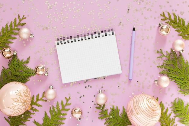 Праздничный фон, новогодние шары и веточки туи на розовом фоне с блестящими серебряными звездами, открытый спиральный блокнот и ручка, плоская планировка, вид сверху