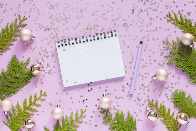 Holiday background , christmas balls and thuja twigs on a lilac background with glitter silver stars, open spiral notepad and pen, flat lay, top view