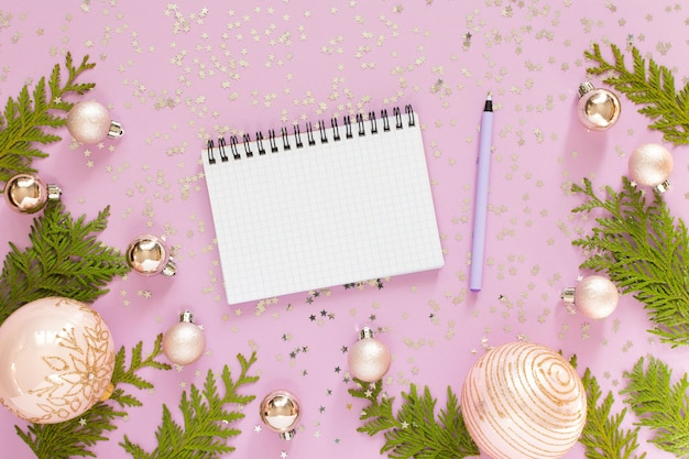 Holiday background , christmas balls and thuja twigs on a pink background with glitter silver stars, open spiral notepad and pen, flat lay, top view
