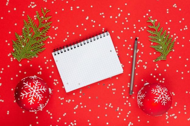 휴일 배경, 반짝이는 은색 별이 있는 빨간색 배경에 눈송이와 thuja 나뭇가지가 있는 크리스마스 공, 열린 나선형 메모장 및 펜, 평평한 평지, 위쪽 전망