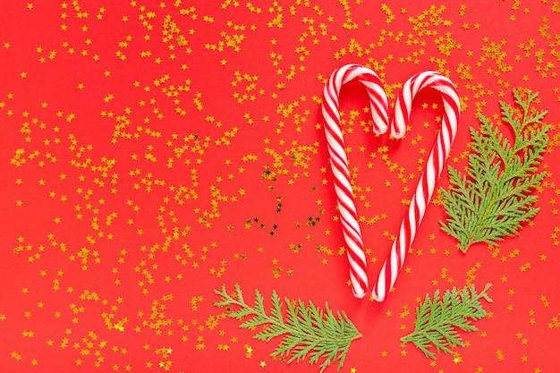 휴일 배경, 하트 모양의 크리스마스 사탕 지팡이, 반짝이는 금색 별이 있는 빨간색 배경에 있는 thuja 잔가지