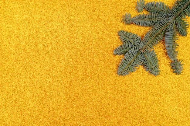 休日の背景。金色の背景にクリスマスツリーの枝。