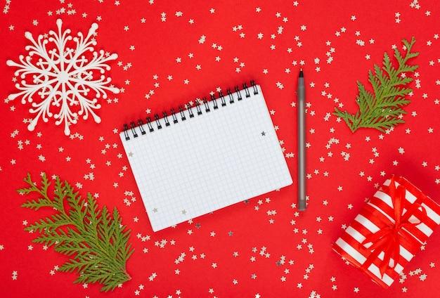 휴일 배경, 선물 상자, 눈송이 및 thuja 나뭇가지가 반짝이는 은색 별, 열린 나선형 메모장 및 펜, 평평한 평지, 위쪽 전망이 있는 빨간색 배경에
