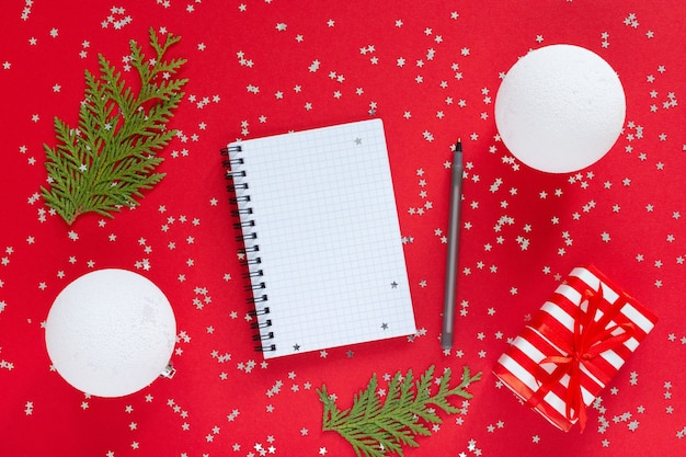Holiday background , gift box with ribbon and bow and christmas balls and thuja twigs on a red background with glitter silver stars, open spiral notepad and pen, flat lay, top view