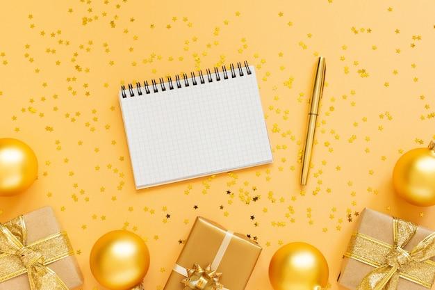 휴일 배경, 선물 상자와 반짝이 골드 크리스마스 공 골드 배경, 열린 나선형 메모장 및 펜, 평면 평신도, 평면도, 복사 공간