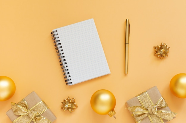 休日の背景、ゴールドの背景にギフト ボックスとキラキラ ゴールド クリスマス ボール、開いたスパイラル メモ帳とペン、フラット レイアウト、トップ ビュー、コピー スペース