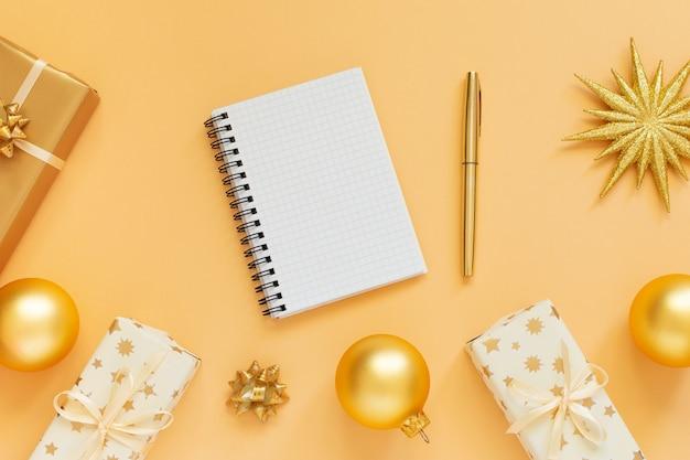휴일 배경, 반짝이 골드 스타와 선물 상자와 크리스마스 공, 열린 나선형 메모장 및 펜, 평면 평신도, 평면도, 복사 공간 골드 배경