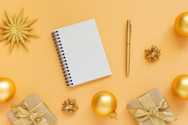 Holiday background, gold background with glitter gold star and gift boxes and christmas balls, open spiral notepad and pen, flat lay, top view, copy space
