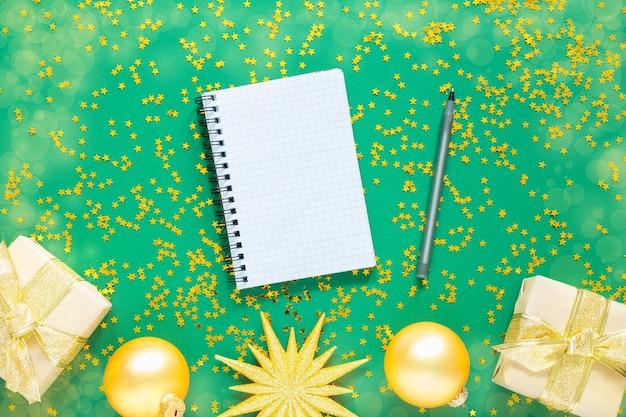 휴일 배경, 골드 크리스마스 공 및 전나무 나뭇 가지와 반짝이 골드 별, 열린 나선형 메모장 및 펜, 평면 누워, 평면도와 녹색 배경에 밝은 반짝이 크리스마스 화환