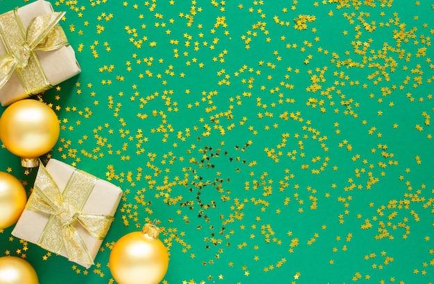 반짝이는 금색 별, 평평한 평지, 위쪽 전망이 있는 녹색 배경에 휴일 배경, 금색 크리스마스 공 및 선물 상자
