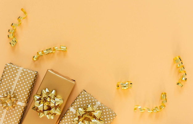 Holiday background in gold colors, gift boxes with shiny bows and with glitter ribbons serpentine on a gold background, flat lay, top view, copy space