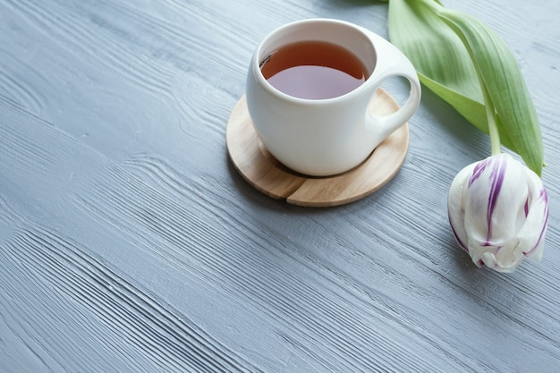 Праздничный фон. открытка. белая чашка с чаем, розовые тюльпаны. место для текста.
