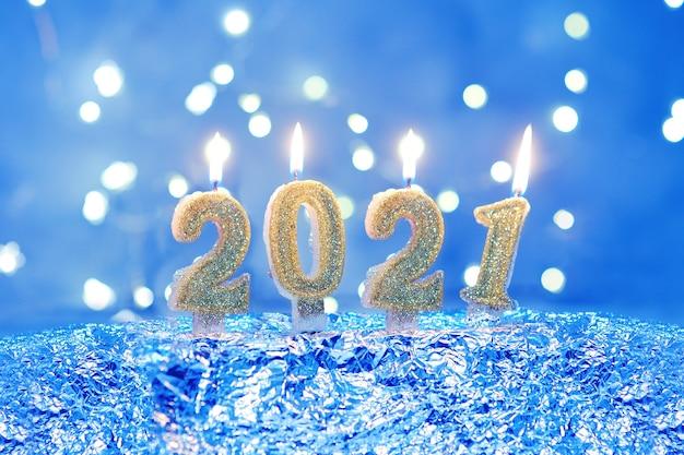 Праздничный фон с новым 2021 годом. цифры 2021 года сделаны золотыми зажженными свечами.