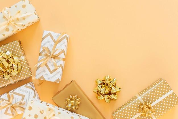 금색의 휴일 배경, 금색 배경에 활이 있는 선물 상자, 평평한 평지, 위쪽 전망, 복사 공간
