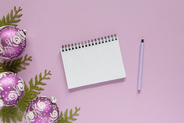 휴일 배경, 라일락 크리스마스 공 및 thuja 나뭇가지, 분홍색 배경, 열린 나선형 메모장 및 펜, 평평한 평지, 위쪽 전망