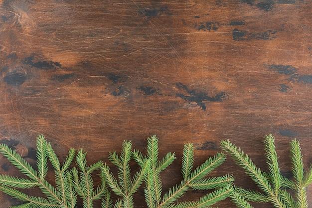 Праздничный фон рождественских еловых веток, ели, можжевельника, пихты, лиственницы, сосновых шишек со светом. рождество и новогодняя тема. плоская планировка, вид сверху