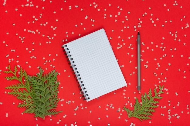 휴일 배경, 열린 나선형 메모장, 펜 및 thuja 나뭇가지가 반짝이는 은색 별, 평평한 평지, 위쪽 전망이 있는 빨간색 배경에 있습니다.