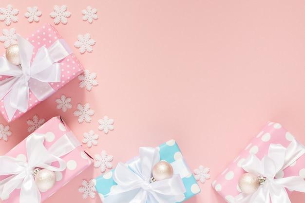 Праздничный фон, розовые и синие подарочные коробки в горошек с белой лентой и бантом и рождественские шары на розовом фоне со снежинками, плоская планировка, вид сверху