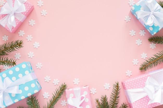 휴일 배경, 흰색 리본과 활과 가문비 나무 가지가있는 물방울 무늬의 분홍색과 파란색 선물 상자