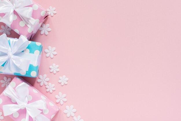 休日の背景、水玉模様のピンクと青のギフト ボックスに白いリボンと、ピンクの背景に雪の結晶、フラット レイアウト、トップ ビューの弓
