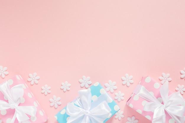 Праздничный фон, розовые и синие подарочные коробки в горошек с белой лентой и бантом на розовом фоне со снежинками, плоская планировка, вид сверху