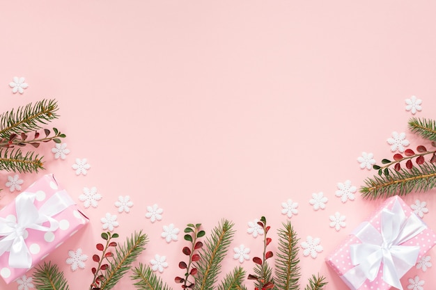 Holiday background , pink gift boxes in polka dots with white ribbon and bow and spruce branches on a pink background with snowflakes , flat lay, top view
