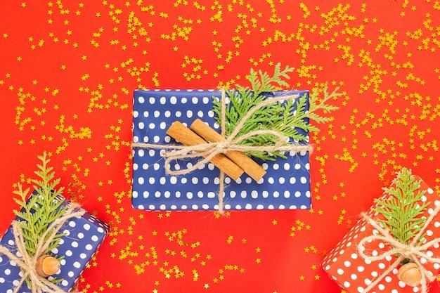 ホリデー背景、水玉模様の赤と青のギフト ボックスにリボンと弓と thuja の小枝と赤の背景にキラキラの金の星、フラット レイアウト、トップ ビュー
