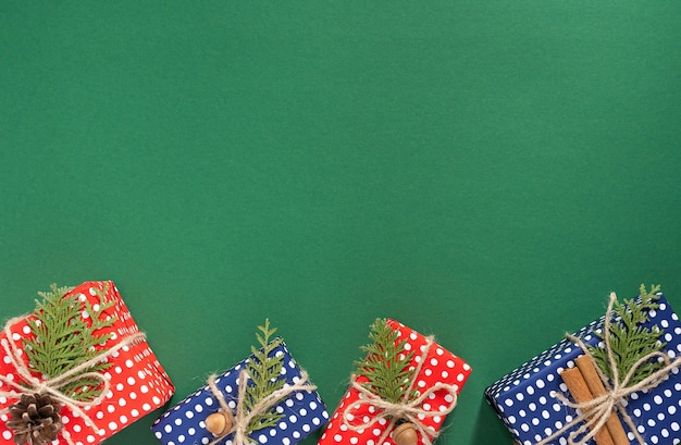 Holiday background , red and blue gift boxes in polka dots and thuja twigs with christmas tree cone and acorn on green background, merry christmas and happy new year concept, flat lay, top view