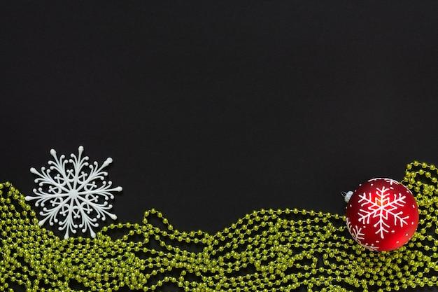휴일 배경, 빨간색 크리스마스 공, 눈송이 및 검정색 배경에 녹색 밝은 장식 구슬, 평평한 평지, 위쪽 보기