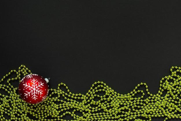 휴일 배경, 눈송이와 검정색 배경에 녹색 밝은 장식 구슬이 있는 빨간색 크리스마스 공, 평평한 평지, 위쪽